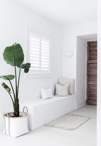 Image of a white bench seat with white cushions and single plant in a white pot
